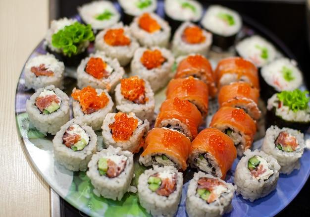 Thuis sushi en broodjes maken. sushi met zeevruchten, salade en witte rijst. eten voor familie en vrienden. een set van verschillende broodjes en sushi op een dienblad.