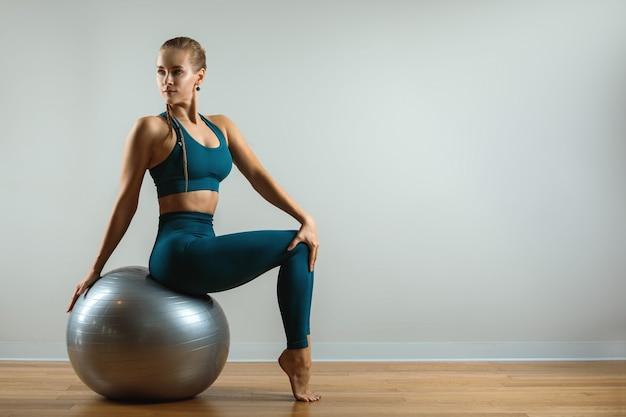 Thuis trainen. fitnesstrainer met fitball op een grijze achtergrond. trainingen met verschillende spotvoorraad. kopieer de ruimte, fitness baren.