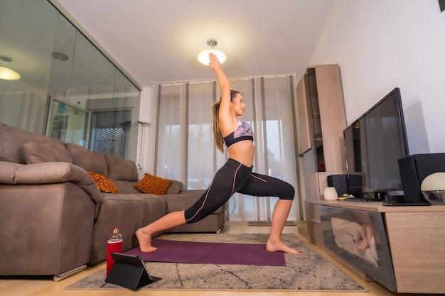 Thuis trainen in een online klas, blanke blonde doet oefeningen in haar woonkamer op de knielende mat