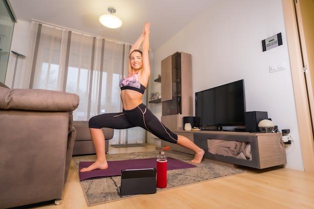 Thuis trainen in een online klas, blonde blanke meisje doet oefeningen in haar kamer op de mat