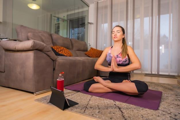 Thuis trainen in een online klas, blonde blanke vrouw doet yoga adem in haar woonkamer op de mat