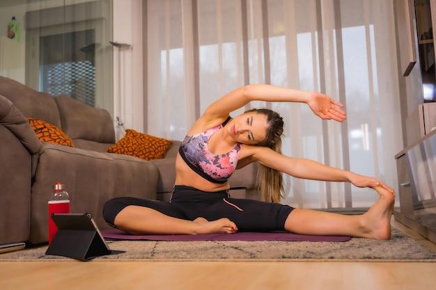 Thuis trainen met in een online klas, blanke vrouw doet yoga-oefeningen en kijkt naar de tablet