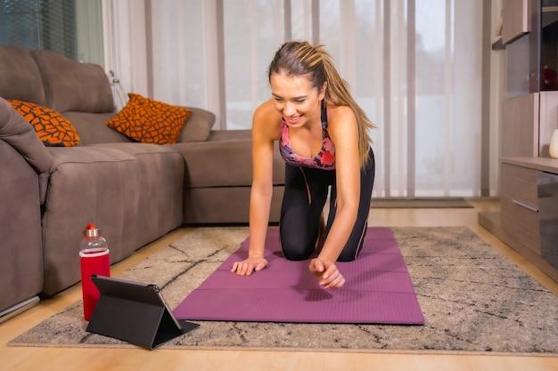 Thuis trainen met in een online klas, blanke vrouw doet yoga thuis op de mat