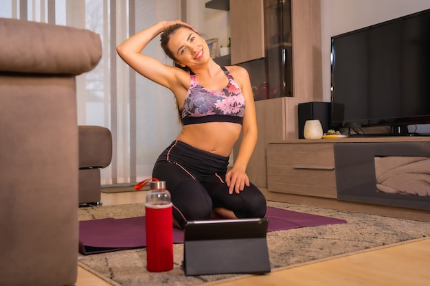 Thuis trainen met in een online klas, blonde blanke vrouw doet oefeningen in haar woonkamer op de knielende mat