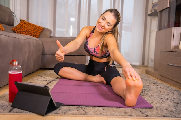 Thuis trainen met in een online klas, kaukasisch yoga-oefeningen doen en goedkeuring geven op de tablet aan de monitor