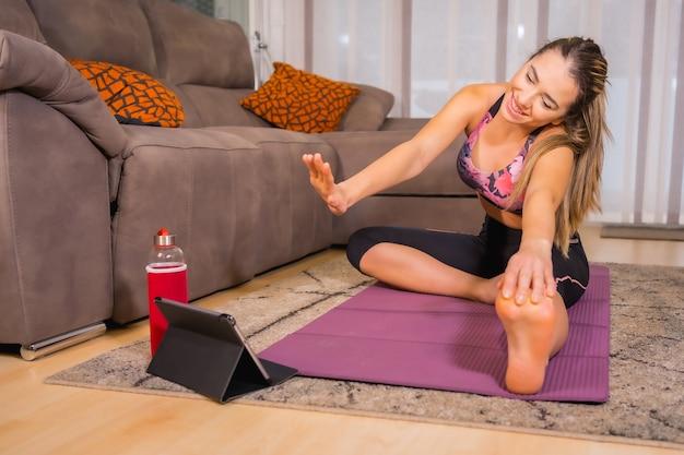 Thuis trainen met in een online klas, kaukasisch yoga-oefeningen doen en hallo zeggen tegen de monitor op de tablet