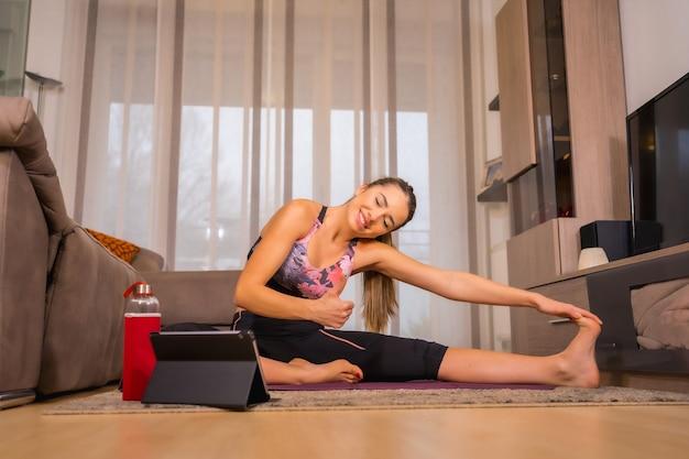 Thuis trainen met in een online klas, kaukasisch yoga-oefeningen doen en heel graag naar de tablet kijken