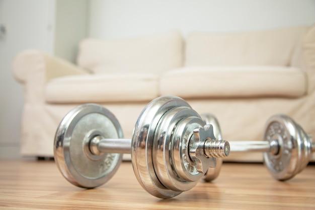 Thuis training krachttraining met halter concept en bank achtergrond.
