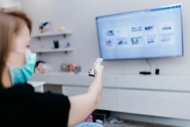 Thuis tv kijken in zelfisolatie in quarantaine wissel van tv-zender met de afstandsbediening