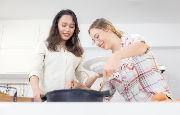 Thuis vermaken twee vriendjes zich in de keuken. zusters bereiden samen spaghetti in de keuken. in de keuken, twee vrouwelijke maatjes