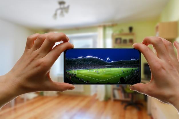 Thuis voetbal kijken via smartphone. uitzending van voetbal vanuit het stadion.