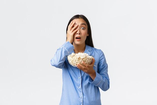 Thuis vrije tijd, logeerpartij en slaapfeestje concept. geschokt aziatisch meisje in pyjama's met popcorn, hijgend en geschrokken op zoek, open mond met belangstelling als tv of film kijken, witte muur.