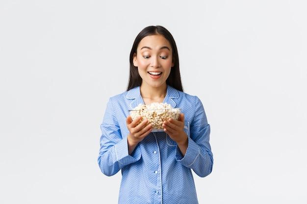 Thuis vrije tijd, logeerpartij en slaapfeestje concept. opgewonden glimlachend aziatisch meisje in pyjama's die verleidelijk kijken naar smakelijke kom popcorn, bereide snacks voor filmavond, witte muur.