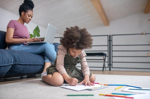 Thuis weekdagen. klein meisje met donkere huidskleur zittend op de vloer en jonge vrouw met laptop op de bank thuis
