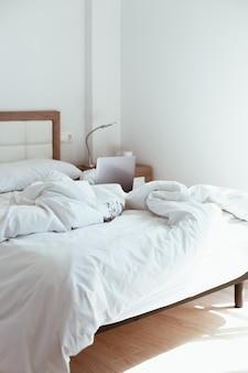 Thuis werken. laptop in onopgemaakt bed. comfortabel en gezellig thuiskantoor op afstand.