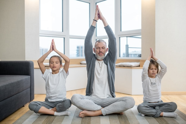 Thuis yoga. vader en zijn kinderen doen thuis samen yoga en zien er vredig uit