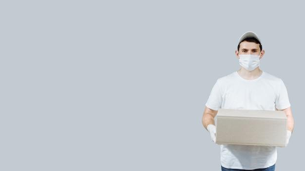 Thuisbezorging werknemer werknemer in witte pet lege t-shirt uniforme gezichtsmasker handschoenen houden een lege kartonnen doos