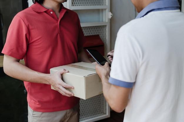 Thuisbezorgservice man in rode uniform en jonge man klant handtekening toevoegen