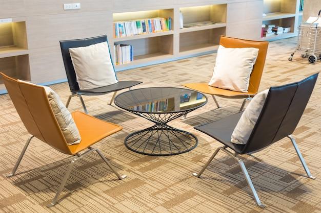 Thuisbibliotheek met boekenplanken met stoelen ernaartoe.