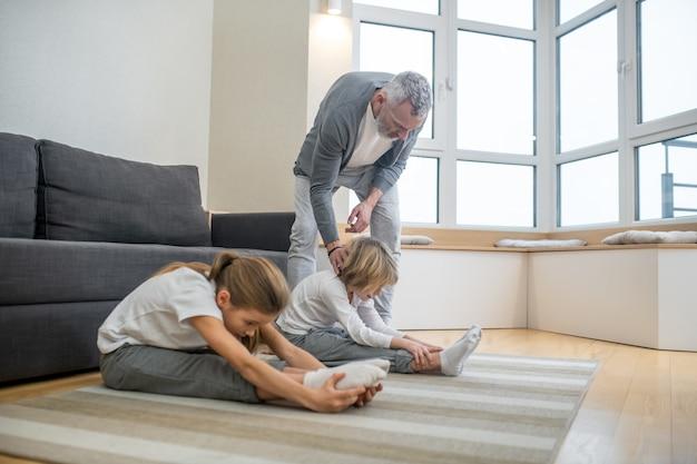 Thuiscoach. vader traint zijn kinderen thuis en zorgt ervoor dat ze zich correct uitrekken