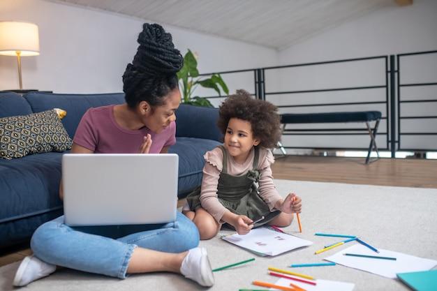 Thuiscomfort. jonge afro-amerikaanse vrouw met laptop en klein lachend meisje met potloden en papier zittend op de vloer communicerend thuis
