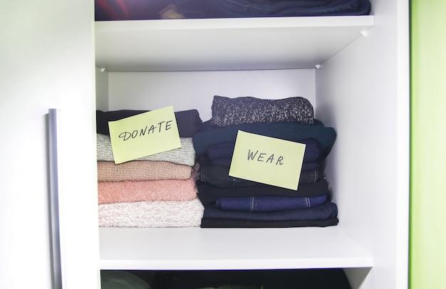 Thuisgarderobe met verschillende kleding gesorteerd voor donatie.