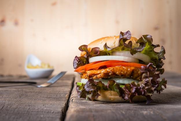 Thuisgemaakte kipburger met frites, sla, tomaat en ui op houten boord.