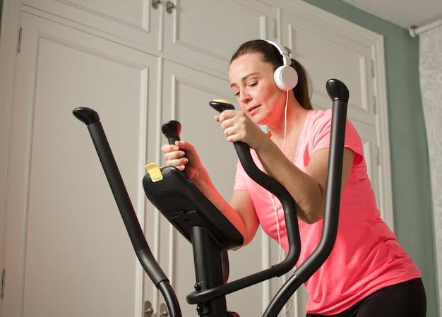 Thuisgym. actieve vrouw been oefening op elliptische trainer thuis met koptelefoon