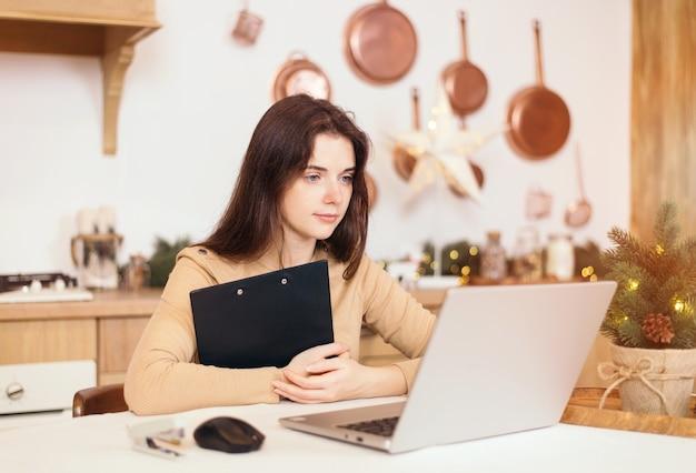 Thuiskantoor concept. jonge vrouw freelancer zit aan een tafel thuis in een lichte keuken in de winter