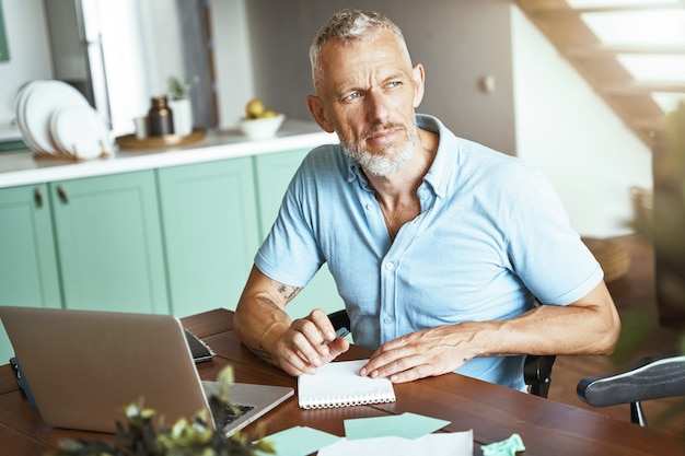 Thuiskantoor gerichte blanke man van middelbare leeftijd die wat aantekeningen maakt terwijl hij aan tafel zit en werkt