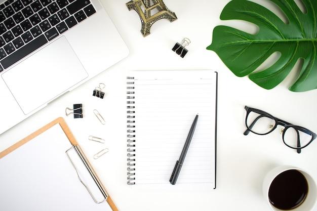 Thuiskantoor werkruimte met een laptop, palmblad, notebook en accessoires. plat leggen, plat leggen, kopie ruimte bovenaanzicht.