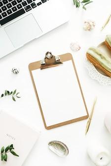 Thuiskantoor werkruimte met klembord, laptop, notebook en stijlvolle spullen. platliggend, bovenaanzicht