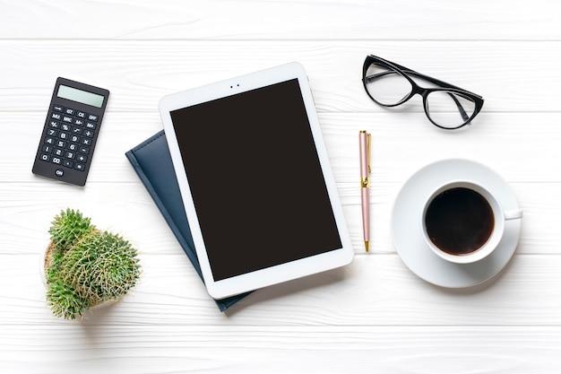 Thuiskantoor werkruimte. tablet, glazen, kladblok, kopje koffie, pen, sappig op witte houten tafel