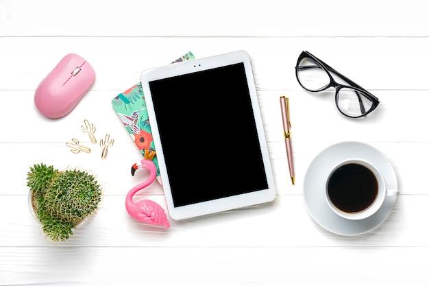 Thuiskantoor werkruimte. tablet, rekenmachine, blocnote, gouden pen en clips, glazen, flamingobeeldje, kopje koffie, sappig, pc-muis op witte houten tafel
