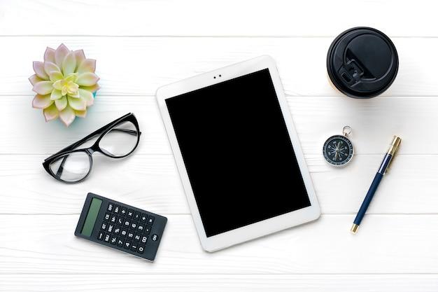 Thuiskantoor werkruimte. tablet, rekenmachine, kladblok, gouden pen en clips, glazen, kopje koffie, sappig op witte houten tafel