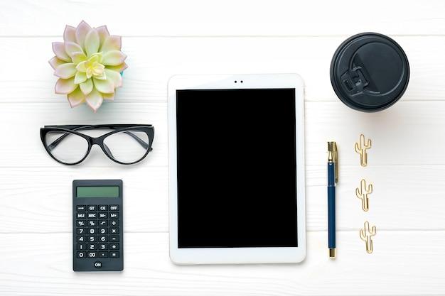 Thuiskantoor werkruimte. tablet, rekenmachine, notitieblok, gouden pen en clips, glazen, kopje koffie