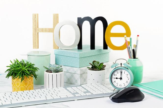 Thuiskantoorconcept met bloemen in de potten en kantoorbenodigdheden, computertoetsenbord en muis
