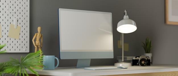 Thuiskantoorruimte met een leeg scherm, computerfiguurcamera en decor op bureau en grijze muur