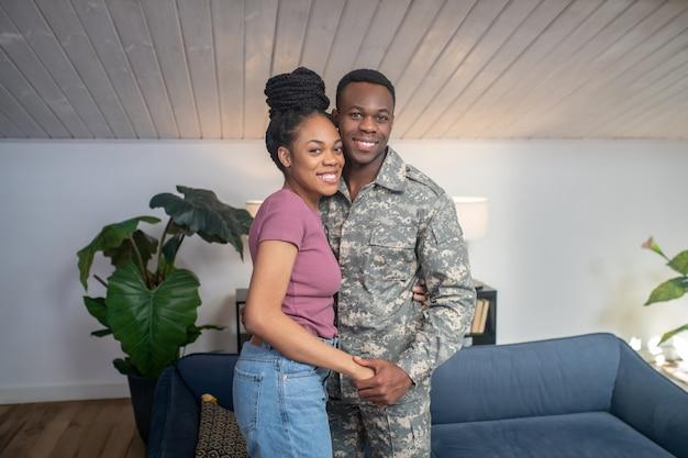 Thuiskomst. donkerhuidige jonge volwassen glimlachende vrouw in t-shirt en jeans en militaire man in camouflage die thuis in de kamer staat?