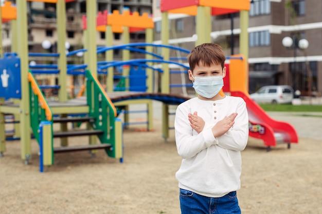 Thuismodus en zelfisolatie tijdens quarantaine en epidemieën. acht jaar oude jongen in de speeltuin in een medisch masker toont met zijn handen het stopteken. kinderopvang en gezondheid