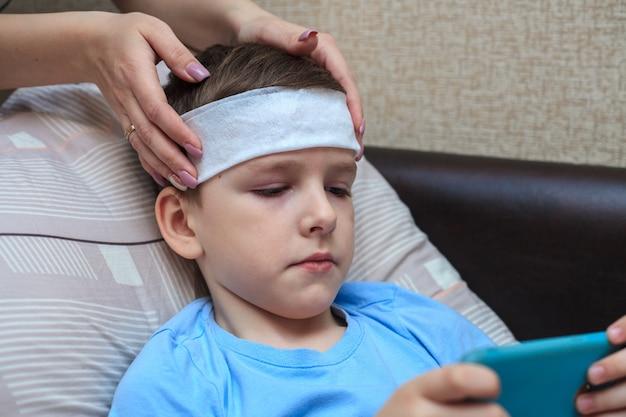 Thuisquarantaine. een natte handdoek op het voorhoofd van een kind. hoofdpijn en koorts bij een jongen.