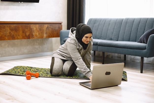 Thuissport voor moslimvrouwen. glimlachend arabisch meisje in hijab die online yoga beoefent, video-tutorial op laptop bekijkt, oefeningen doet in de woonkamer