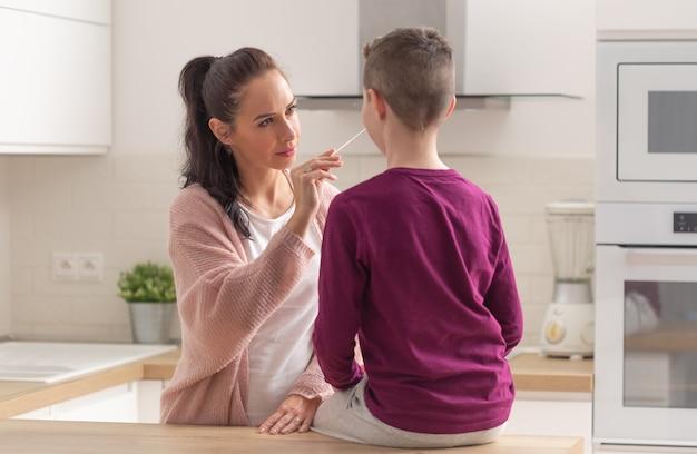 Thuistesten voor covid-19 terwijl moeder een wattenstaafje in de neus van haar zoon stopt die op een keukenbureau zit.