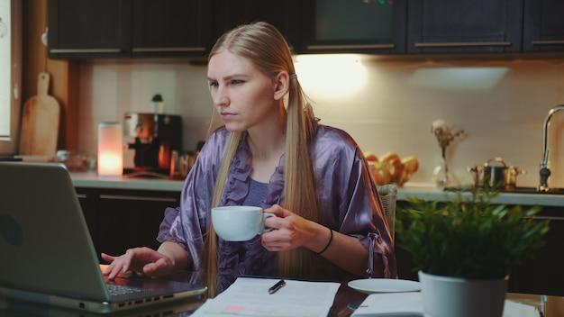 Thuiswerken. bezige vrouw die in huisbadjas een kop van koffie drinkt