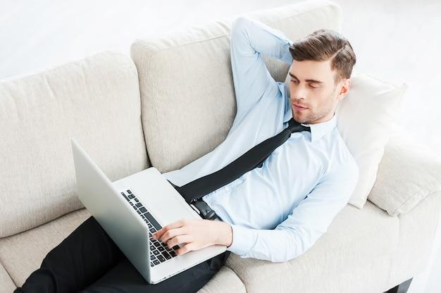 Thuiswerken. bovenaanzicht van jonge zakenman die op laptop werkt en hand achter het hoofd houdt
