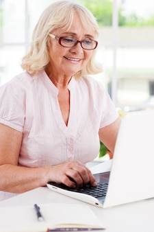 Thuiswerken. gelukkige senior vrouw die aan de laptop werkt en glimlacht terwijl ze aan tafel zit