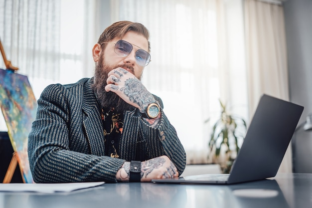 Thuiswerken. man gekleed in modieus pak met zonnebril zit aan tafel met een laptop. brute kerel en zijn werk op afstand.