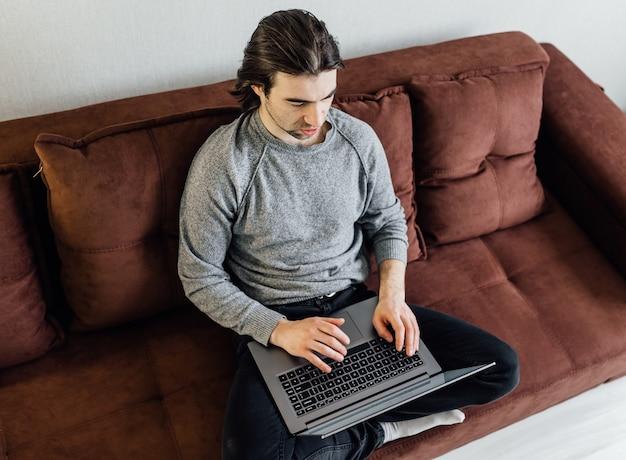 Thuiswerken, thuiskantoor. een jonge kerel in vrijetijdskleding gebruikt laptop voor online communicatie. hij zit op de bank, kijkt naar het scherm van de laptop en spreekt