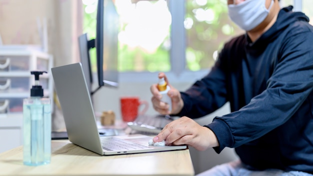 Thuiswerken (wfh). computer schoonmaken voor gebruik. vergrendelen en thuis in quarantaine plaatsen. sociale afstand en fysieke afstand. blijf thuis blijf veilig. effect van covid-19 en stop uitbraakvirus.