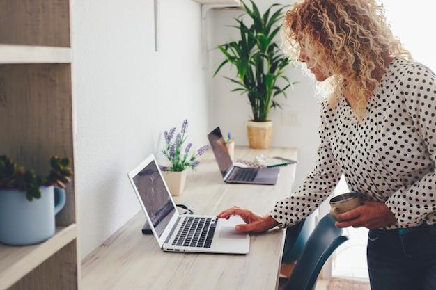 Thuiswerkplek desktop en zakenvrouw met behulp van laptopcomputer om meldingen te controleren of berichten te verzenden. concept van slimme werkende moderne vrouwelijke mensen die bezig zijn met online baanwinkelzaken
